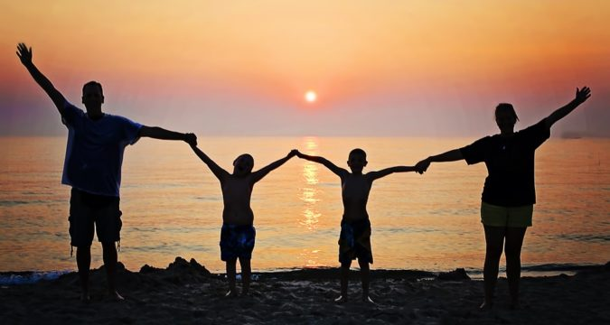 Happy family of four together on the beach in front of the sunset
