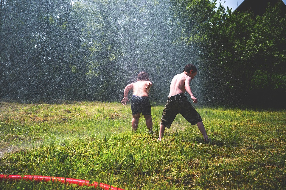 Two brothers playing outside together in a sprinkler